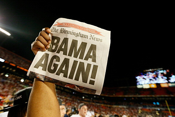 A member of the Alabama Crimson Tide holds up a newpaper