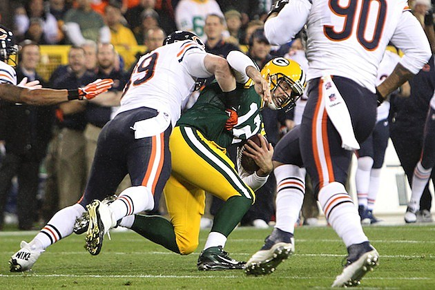 Shea McClellin #99 of the Chicago Bears tackles Aaron Rodgers #12 of the Green Bay Packers